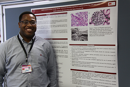 Grant Pierre stands next to the poster for his research project, ready to answer questions.